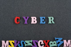 Palabra CIBERNÉTICA en el fondo negro compuesto de letras de madera del ABC del bloque colorido del alfabeto, espacio del tablero Fotografía de archivo libre de regalías