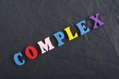 Palabra COMPLEJA en el fondo negro compuesto de letras de madera del ABC del bloque colorido del alfabeto, espacio del tablero de Foto de archivo libre de regalías