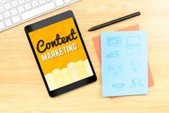 Palabra contenta del márketing en la pantalla de la tableta con el icono en notebo azul Foto de archivo libre de regalías