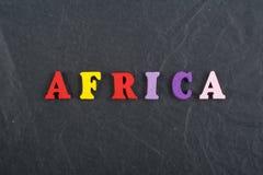 Palabra de ÁFRICA en el fondo negro compuesto de letras de madera del ABC del bloque colorido del alfabeto, espacio del tablero d Fotos de archivo libres de regalías