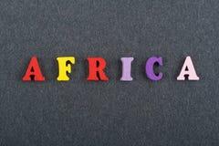 Palabra de ÁFRICA en el fondo negro compuesto de letras de madera del ABC del bloque colorido del alfabeto, espacio del tablero d Imagen de archivo libre de regalías
