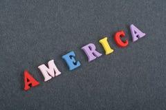 Palabra de América en el fondo negro compuesto de letras de madera del ABC del bloque colorido del alfabeto, espacio del tablero  Imagen de archivo libre de regalías