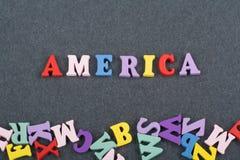 Palabra de América en el fondo negro compuesto de letras de madera del ABC del bloque colorido del alfabeto, espacio del tablero  Imagenes de archivo