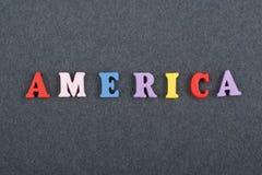 Palabra de América en el fondo negro compuesto de letras de madera del ABC del bloque colorido del alfabeto, espacio del tablero  Foto de archivo libre de regalías