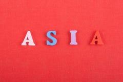 Palabra de ASIA en el fondo rojo compuesto de letras de madera del ABC del bloque colorido del alfabeto, espacio de la copia para Imagen de archivo