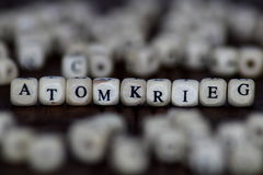 Palabra de ATOMKRIEG escrita en el cubo de madera con el fondo de los dados fotos de archivo libres de regalías