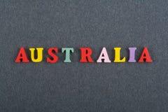 Palabra de AUSTRALIA en el fondo negro compuesto de letras de madera del ABC del bloque colorido del alfabeto, espacio del tabler Imagen de archivo libre de regalías