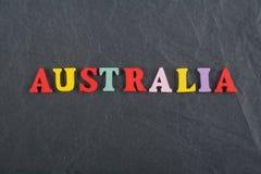 Palabra de AUSTRALIA en el fondo negro compuesto de letras de madera del ABC del bloque colorido del alfabeto, espacio del tabler Imagen de archivo