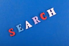 Palabra de BÚSQUEDA en el fondo azul compuesto de letras de madera del ABC del bloque colorido del alfabeto, espacio de la copia  Fotografía de archivo