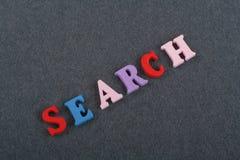 Palabra de BÚSQUEDA en el fondo negro compuesto de letras de madera del ABC del bloque colorido del alfabeto, espacio del tablero Fotos de archivo libres de regalías