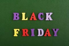 Palabra de BLACK FRIDAY en el fondo verde compuesto de letras de madera del ABC del bloque colorido del alfabeto, espacio de la c Fotos de archivo