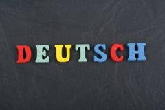 Palabra de DEUTSCH en el fondo negro compuesto de letras de madera del ABC del bloque colorido del alfabeto, espacio del tablero  Foto de archivo
