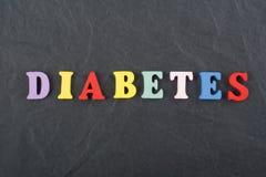 Palabra de DIABETETES en el fondo negro compuesto de letras de madera del ABC del bloque colorido del alfabeto, espacio del table Fotos de archivo libres de regalías