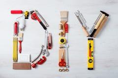 Palabra de DIY integrada por las herramientas del trabajo fotografía de archivo