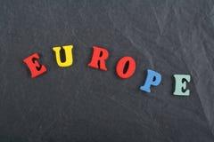 Palabra de EUROPA en el fondo negro compuesto de letras de madera del ABC del bloque colorido del alfabeto, espacio del tablero d Fotos de archivo