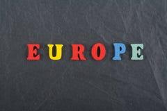 Palabra de EUROPA en el fondo negro compuesto de letras de madera del ABC del bloque colorido del alfabeto, espacio del tablero d Fotografía de archivo