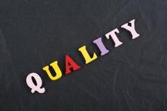 Palabra de GUALITY en el fondo negro compuesto de letras de madera del ABC del bloque colorido del alfabeto, espacio del tablero  foto de archivo libre de regalías