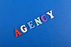 Palabra de la AGENCIA en el fondo azul compuesto de letras de madera del ABC del bloque colorido del alfabeto, espacio de la copi Fotografía de archivo
