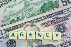 Palabra de la agencia en fondo del dólar Concepto de las finanzas Imágenes de archivo libres de regalías
