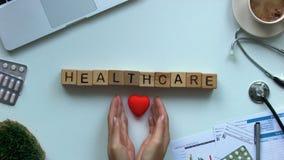 Palabra de la atención sanitaria en los cubos, manos de los doctores que ponen el corazón en la tabla, cardiología del juguete metrajes