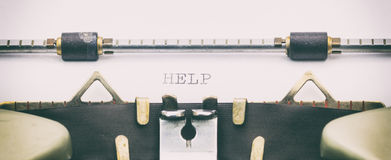 Palabra de la AYUDA con mayúsculas en una hoja de la máquina de escribir Imagenes de archivo
