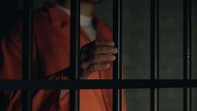 Palabra de la ayuda escrita en los fingeres del preso, barras masculinas de la cárcel de la tenencia, malos tratamientos almacen de video