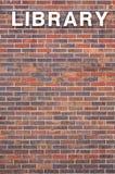Palabra de la biblioteca en la pared de ladrillo Foto de archivo libre de regalías