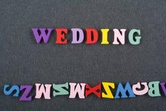 Palabra de la BODA en el fondo negro compuesto de letras de madera del ABC del bloque colorido del alfabeto, espacio del tablero  Imagen de archivo