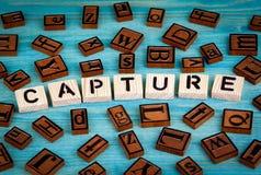 Palabra de la captura escrita en el bloque de madera Alfabeto de madera en un fondo azul imágenes de archivo libres de regalías