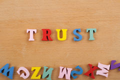 Palabra de la CONFIANZA en el fondo de madera compuesto de letras de madera del ABC del bloque colorido del alfabeto, espacio de  Imagen de archivo