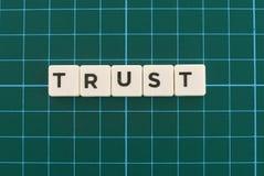 Palabra de la confianza hecha de palabra cuadrada de la letra en fondo cuadrado verde de la estera fotografía de archivo