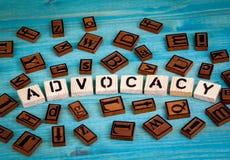 Palabra de la defensa escrita en el bloque de madera Alfabeto de madera en un fondo azul imagen de archivo libre de regalías