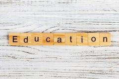 Palabra de la educación del bloque de madera sobre escuela del tablero trasero Palabra de la educación formada por el bloque de m fotografía de archivo