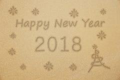 Palabra 2018 de la escritura de la Feliz Año Nuevo con el árbol de navidad y en la arena fina Fotografía de archivo