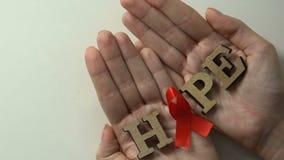 Palabra de la esperanza con la cinta roja en las manos, investigación del tratamiento del VIH, concepto de ahorro de la vida almacen de video