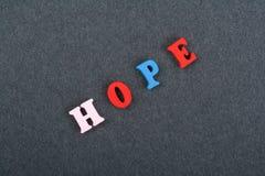 Palabra de la ESPERANZA en el fondo negro compuesto de letras de madera del ABC del bloque colorido del alfabeto, espacio del tab Imágenes de archivo libres de regalías