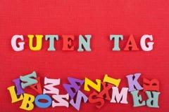Palabra de la ETIQUETA de GUTEN en el fondo rojo compuesto de letras de madera del ABC del bloque colorido del alfabeto, espacio  Imágenes de archivo libres de regalías