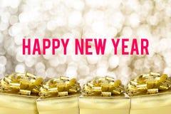 Palabra de la Feliz Año Nuevo con la caja de regalo de oro con la cinta y el colorfu Foto de archivo libre de regalías