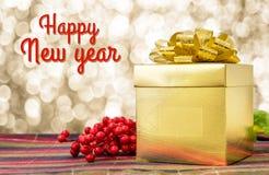 Palabra de la Feliz Año Nuevo con la caja y la cinta del presente del oro en los wi de la tabla Fotografía de archivo libre de regalías