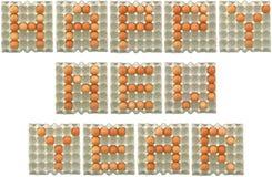 Palabra de la FELIZ AÑO NUEVO de los huevos en la bandeja del papel Imágenes de archivo libres de regalías