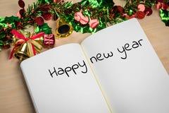 Palabra de la Feliz Año Nuevo en el cuaderno con la decoración del Año Nuevo para nuevo Fotografía de archivo libre de regalías