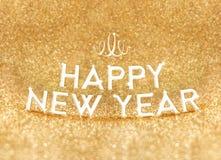 Palabra de la Feliz Año Nuevo en el fondo brillante del brillo del oro, día de fiesta G Fotos de archivo libres de regalías