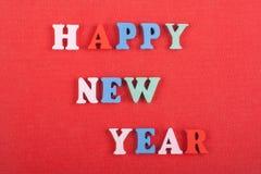 Palabra de la FELIZ AÑO NUEVO en el fondo rojo compuesto de letras de madera del ABC del bloque colorido del alfabeto, espacio de Imagen de archivo libre de regalías