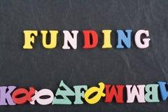 Palabra de la FINANCIACIÓN en el fondo negro compuesto de letras de madera del ABC del bloque colorido del alfabeto, espacio del  Fotos de archivo libres de regalías
