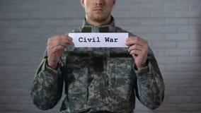 Palabra de la guerra civil escrita en las manos de la muestra adentro del soldado de sexo masculino, de la crueldad y de la muert almacen de metraje de vídeo