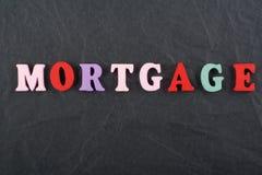 Palabra de la HIPOTECA en el fondo negro compuesto de letras de madera del ABC del bloque colorido del alfabeto, espacio del tabl Fotos de archivo libres de regalías