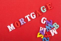 Palabra de la HIPOTECA en el fondo rojo compuesto de letras de madera del ABC del bloque colorido del alfabeto, espacio de la cop Fotografía de archivo