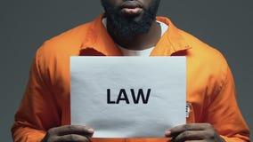 Palabra de la ley en la cartulina en manos de exigir negro del preso, de la orden y de la justicia almacen de metraje de vídeo