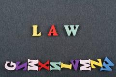 Palabra de la LEY en el fondo negro compuesto de letras de madera del ABC del bloque colorido del alfabeto, espacio del tablero d Foto de archivo libre de regalías