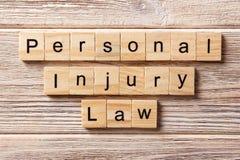 Palabra de la ley de los daños corporales escrita en el bloque de madera texto en la tabla, concepto de la ley de los daños corpo fotografía de archivo libre de regalías